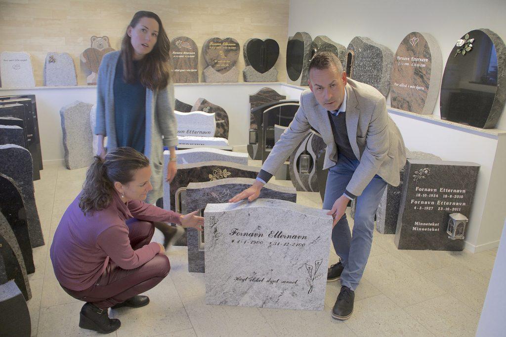 Tre ansatte i Ellingard Monument viser frem gravstein i produksjonslokalene i Vestby